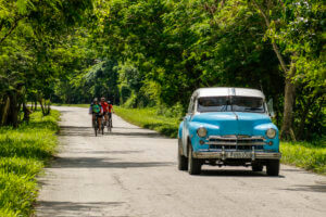 Cycling Group in Rural Cuba along with Classic American Car